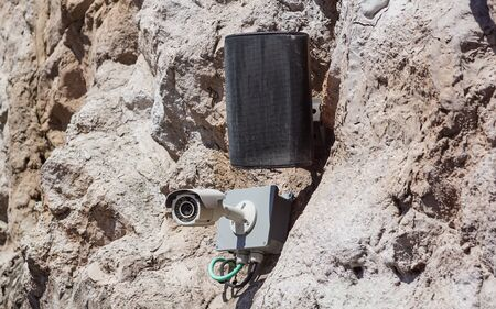 CCTV camera system placed on the rock wall near a speaker Banco de Imagens
