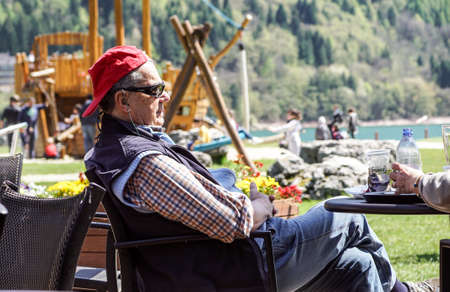 Molveno lake , Italy 15, march 2019 : a man relaxes sitting at a cafe table on a hot summer day near at lake