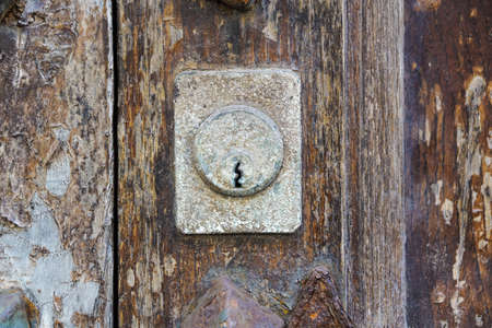 Vintage copper keyhole decorative element on weathered wooden surface