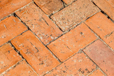 Brick pavement placed in spike, urban background and texture of a spanish courtyard