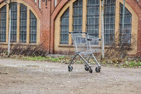 empty shopping cart . trade crisis, abandoned shopping cart in a deserted, empty industrial area. Symbol of the suburbs of abandoned cities or cities in economic crisis.