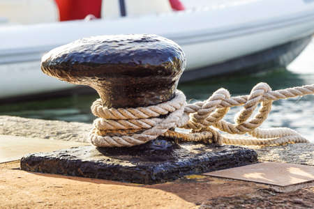 Mooring rope and bollard on sea water and yachts background. Archivio Fotografico
