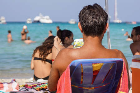 Sardegna , Italy - July 28, 2020 : Unidentified tourists or people they relax by doing leisure activities on the beach in italy Editoriali