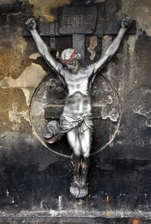 inri: A statue of Jesus Christ crucified on a cross over a grunge background. Stock Photo