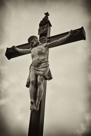 inri: A statue of Jesus Christ crucified on a cross over a grunge background, black and white photo. Stock Photo