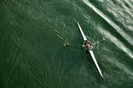 oars: image of a young man rowing in kayak down the river