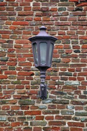 Street lamp on a brick wall textured background photo