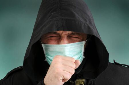 A man with a medical mask covering face, coughing. Stock Photo - 6477200