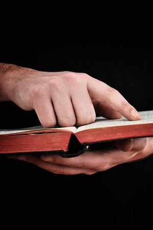 Close up of a man holding a Bible, pointing a verse with his index finger Stock Photo - 6495742
