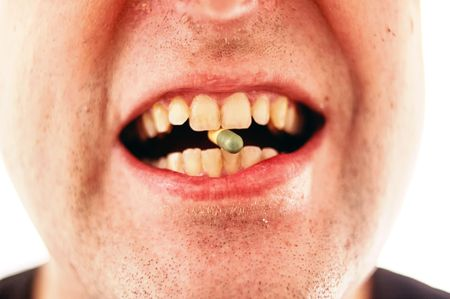 Man holding a pill caplet on his tongue ready to swallow Stock Photo - 6495731