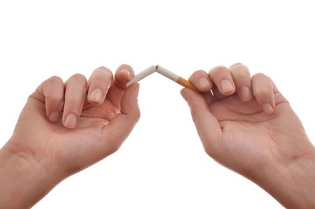 banning the symbol: Quit smoking, hands are breaking a cigarette.