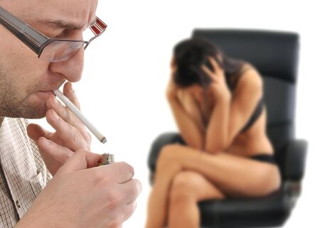 Man is lightning up a cigarette, women in the back sitting nervous photo