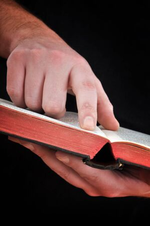 Close up of a man holding a Bible, pointing a verse with his index finger photo