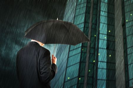 office politics: Businessman is walking toward a corporate building, holding an umbrella. Hard rain fallin. Stock Photo