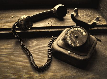 old phone: Very old black telephone device on a dirty wooden shelf Stock Photo