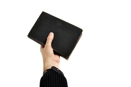 Mans hand is holding a bible, isolated on white background photo