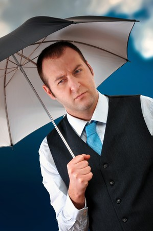 detective agency: Young businessman with umbrella, dark clouds in background. Stock Photo