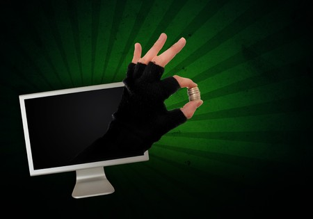 Hand in glove is reaching out from the computer monitor to take your money away, abstract image. Stock Photo - 7450178