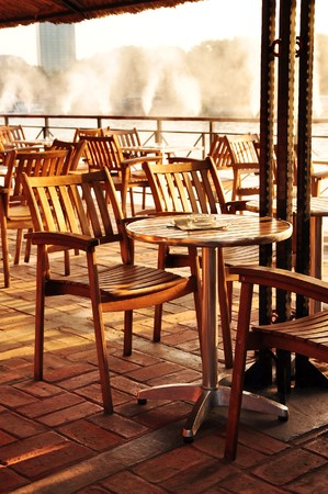 Summer empty open air cafe by the river. photo