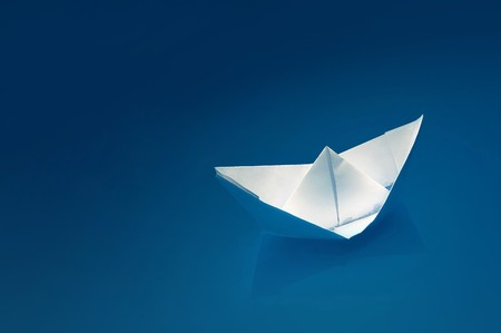 leave: Small white paper ship over a blue background.
