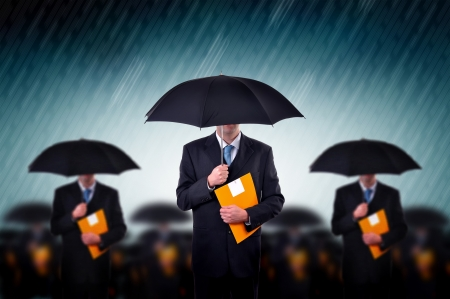 business insurance: Businessman with umbrellas in heavy rain.