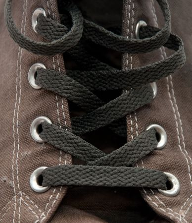 lacing sneakers: closeup detail of a pair of old, dirty gray sneakers