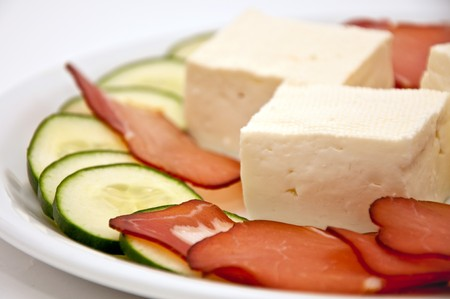 Fresh and tasty goat cheese with slices of red meat, cucumber and  paprika served on a white plate. photo