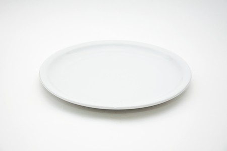 dinner dish: White empty plate over a white background. Stock Photo