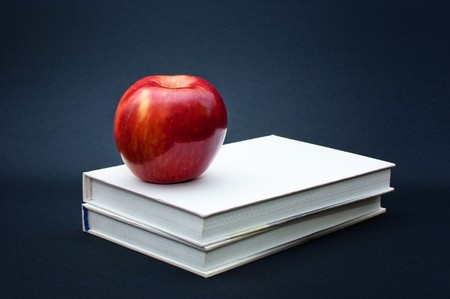 red organic apple placed on the top of two white books Stock Photo - 8022980