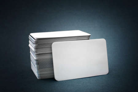 stack of business cards: The pile of blank business cards lays propped up another business card. Stock Photo