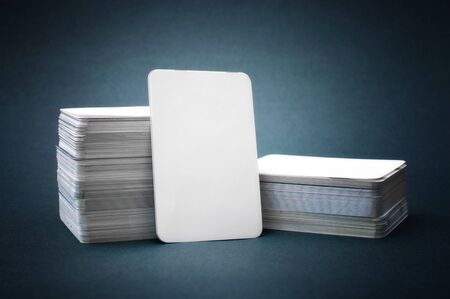 pile up: The pile of blank business cards lays propped up another business card. Stock Photo
