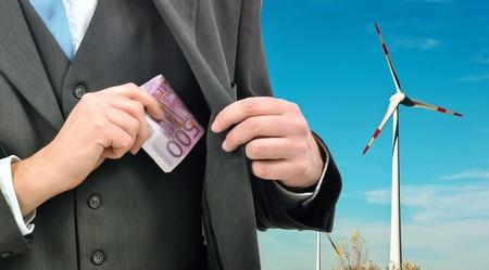 Businessman saving some money using alternative sources of energy - wind turbines. photo