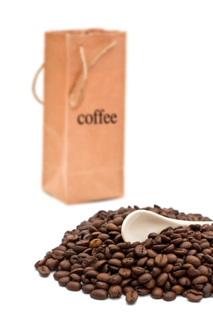 caffiene: Beautiful brown coffee beans, a spoon and a paper bag.