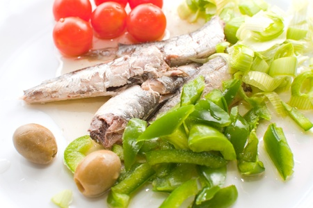 Sardines on a plate served with various vegetables photo