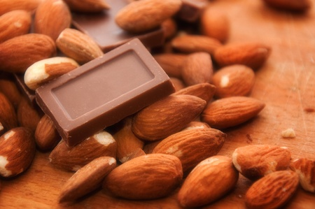 Stack of chocolates and almond, close up image with soft focus photo