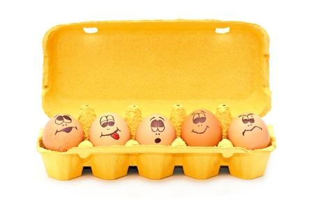 Group of fresh eggs with drawn faces depicting various emotions arranged in a cardboard egg carton against white.