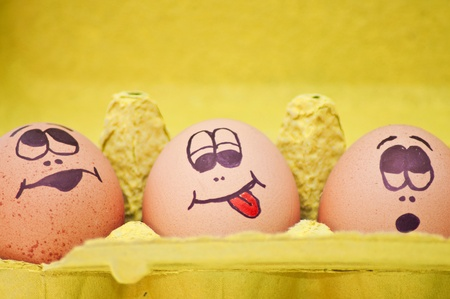 Group of fresh eggs with drawn faces depicting various emotions arranged in a cardboard egg carton against white. photo