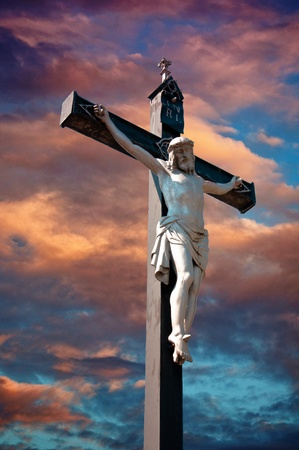 A statue of Jesus Christ crucified against dramatic sky Stock Photo