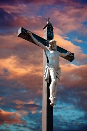 cruz de jesus: Una estatua de Jesucristo crucificado contra cielo dramática Foto de archivo