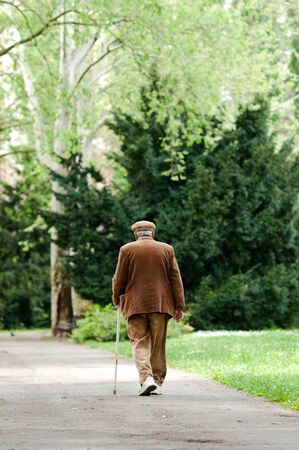 strolling: Elderly man uses a cane to assist him with walking. He is getting some exercise at the park. Stock Photo