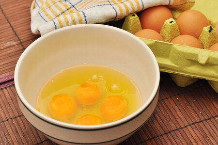 Eggs in an egg tray  in the background and a large mixing bowl with  egg  in the foreground. photo