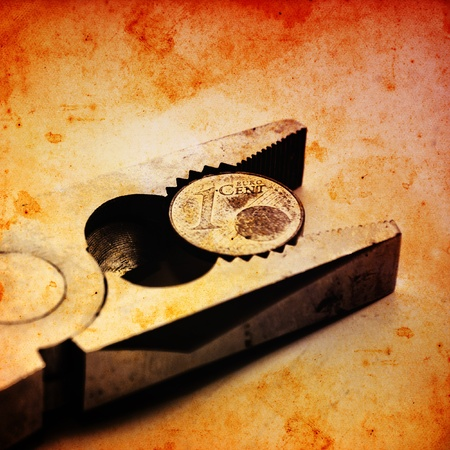 frugality: Euro coin squeezed in a clamp. Stock Photo