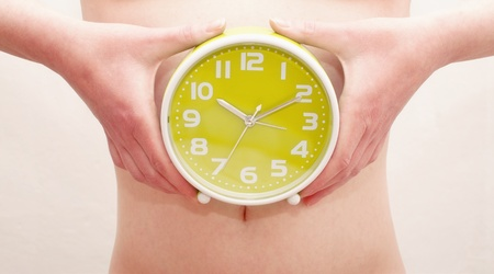 Female hands holding an alarm clock photo