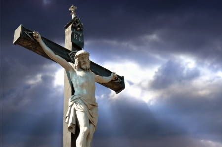 inri: A statue of Jesus Christ crucified against dramatic sky Stock Photo