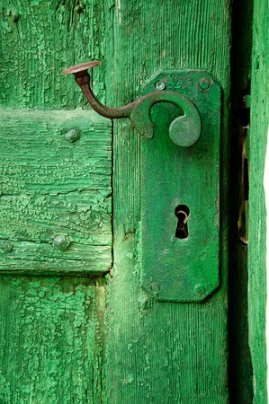 Old ruined green wooden door detail with metal hinge  photo