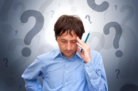 persona confundida: Retrato de un joven empresario sosteniendo un l�piz y pensando.