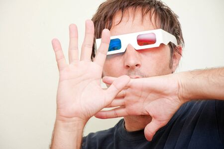 Man with anaglyph 3D glasses making funny face with his hands up. Stock Photo - 9918772