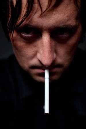 Man smoking cigarette over black background, low key light image photo