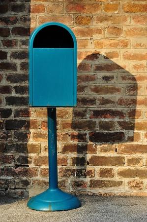 Blue metal trash can against a brick wall photo