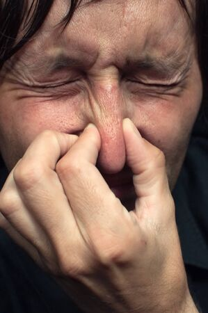 nose close up: Man holding his nose closed because of a bad smell. Stock Photo